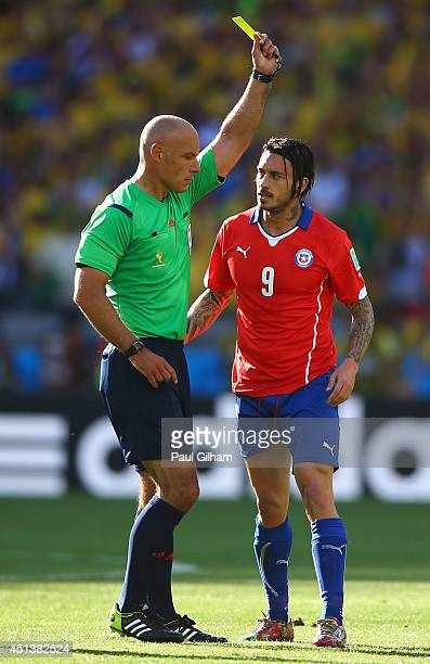 Mauricio Pinilla of Chile is shown a yellow card by referee Howard Webb during the 2014 FIFA World Cup Brazil round of 16 match between Brazil and...