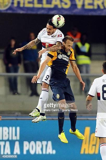 Mauricio Pinilla of Genoa CFC wins a header with Evangelos Moras of Hellas Verona FC during the Serie A match between Hellas Verona FC and Genoa CFC...