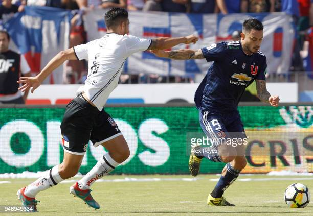 Mauricio Pinilla of U de Chile fights for the ball with Juan Manuel Insaurralde of Colo Colo during a match between U de Chile and Colo Colo as part...