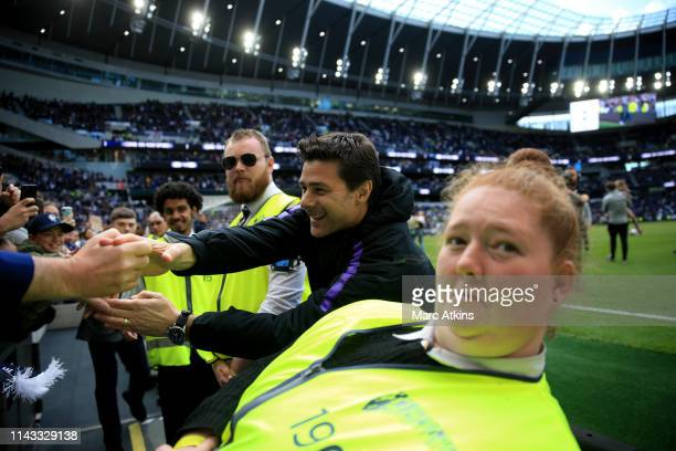 Mauricio Pochettino manager / head coach of Tottenham Hotspur reaches out to a group of fans during the Premier League match between Tottenham...