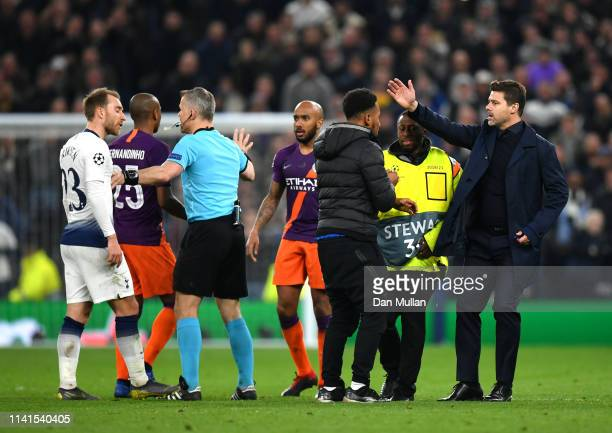 Mauricio Pochettino, Manager of Tottenham Hotspur attempts to get the pitch invader off the pitch as referee Bjorn Kuipers speaks to Christian...