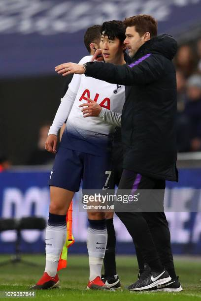 Mauricio Pochettino Manager of Tottenham Hotspur speaks to HeungMin Son of Tottenham Hotspur during the Carabao Cup SemiFinal First Leg match between...