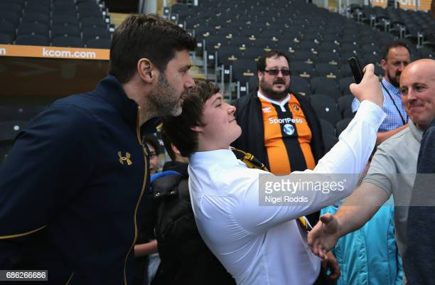 Mauricio Pochettino Manager of Tottenham Hotspur takes a selfie photograph with a fan prior to the Premier League match between Hull City and...
