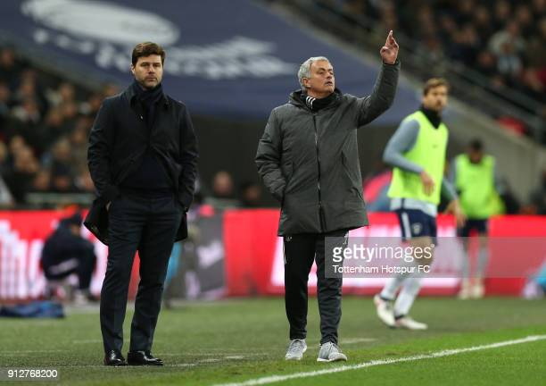 Mauricio Pochettino Manager of Tottlenham Hotspur looks on as Jose Mourinho Manager of Manchester United gives his team instructions during the...
