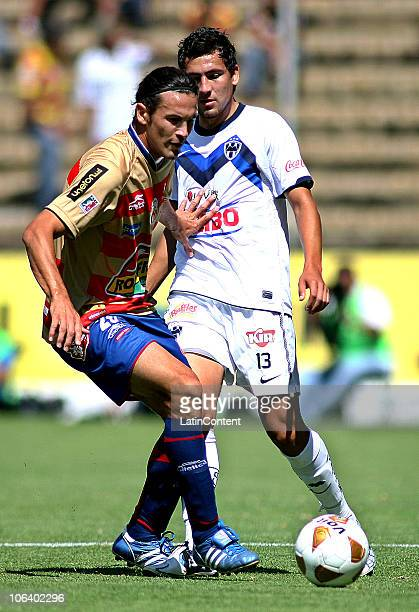 Mauricio Romero of Monarcas Morelia vies for the ball with Abraham Dario Carreno of Monterrey during their match as part of the Apertura 2010 at...