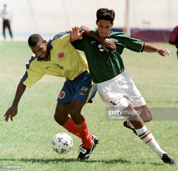 Mauricio Tamayo of Colombia fights for the ball with Eduardo Lillingston from Mexico 17 August during a soccer game in the Pachencho Romero Stadium...