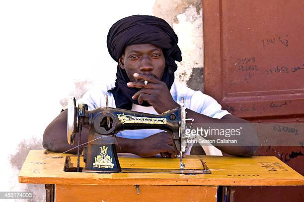 Mauritania, Nouakchott, street tailor with sewing machine. In the cool winter season in North Africa, many persons prefer to work outdoors.