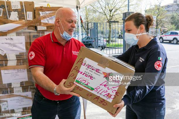 Maurizio Bonomi President of the delegation of the Italian Red Cross of Bergamo passes a box of medical aid arrived from China to his colleague...