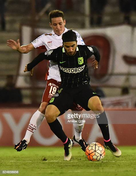 Mauro Bogado of Huracan fights for the ball with Sebastian Perez of Atletico Nacional during a first leg match between Huracan and Atletico Nacional...