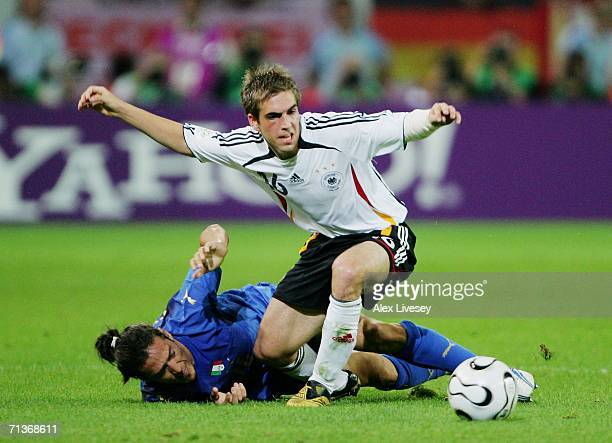 Mauro Camoranesi of Italy falls to the ground after the challenge of Philipp Lahm of Germany during the FIFA World Cup Germany 2006 Semifinal match...