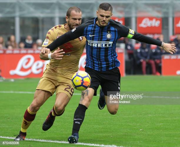 Mauro Emanuel Icardi of FC Internazionale Milano competes for the ball with Lorenzo De Silvestri of Torino FC during the Serie A match between FC...
