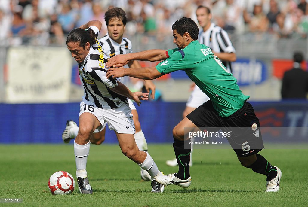Mauro German Camoranesi of Juventus FC is challenged by Miguel Britos of Bologna FC during the Serie A match between Juventus FC and Bologna FC at Olimpico Stadium on September 27, 2009 in Turin, Italy.