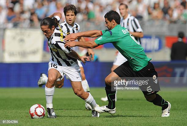 Mauro German Camoranesi of Juventus FC is challenged by Miguel Britos of Bologna FC during the Serie A match between Juventus FC and Bologna FC at...
