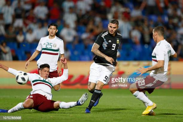 Mauro Icardi of Argentina kicks the ball to score the first goal of his team over Edson Alvarez of Mexico during a friendly match between Argentina...