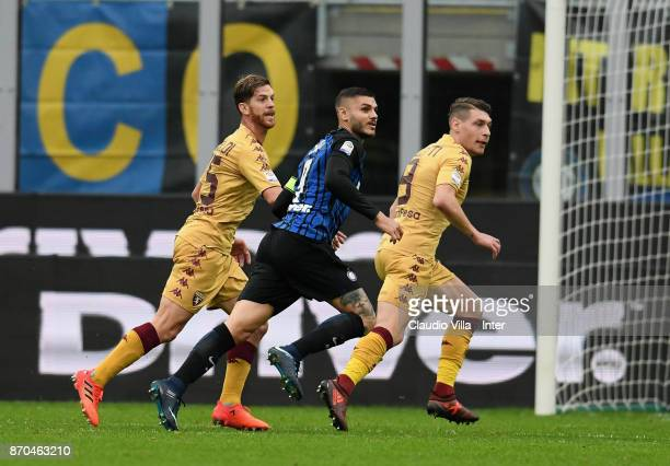 Mauro Icardi of FC Internazionale competes for the ball with Cristian Ansaldi and Andrea Belotti of Torino FC during the Serie A match between FC...