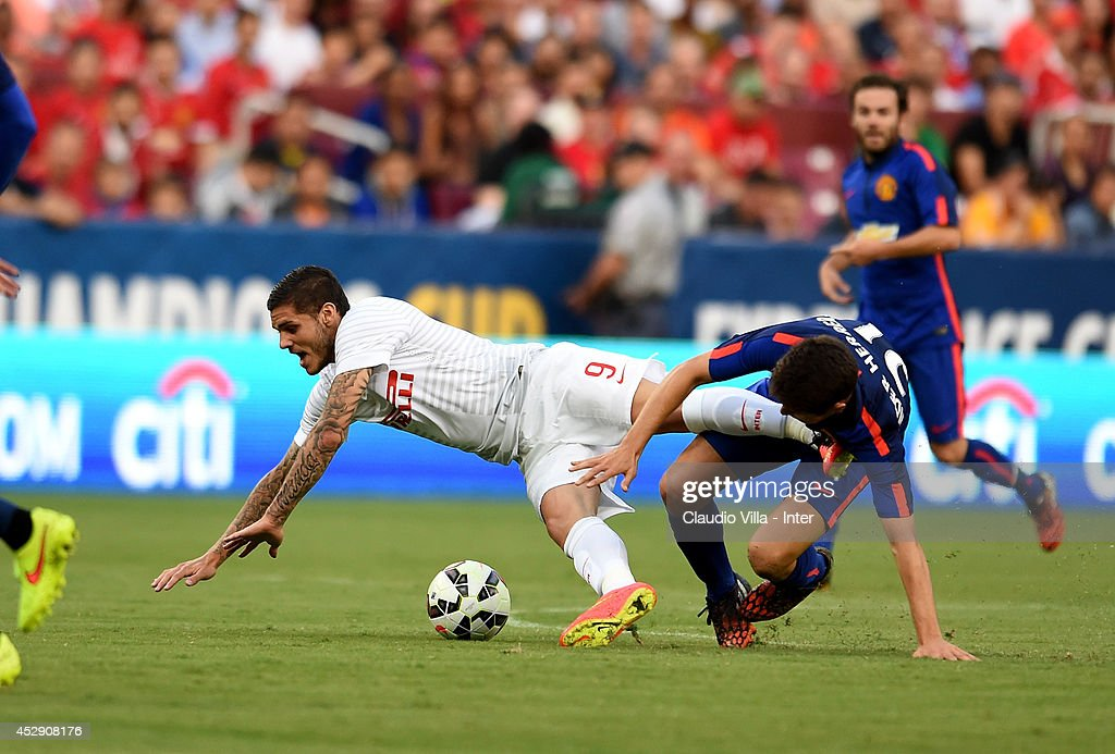 Mauro Icardi #9 of Inter Milan is tripped up by Ander Herrera #21 of Manchester United in the first half during their match in the International Champions Cup 2014at FedExField on July 29, 2014 in Landover, Maryland.