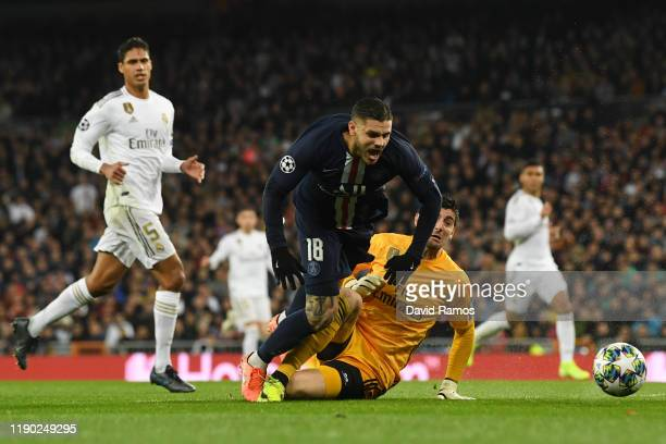 Mauro Icardi of Paris SaintGermain is challenged by Thibaut Courtois of Real Madrid who receives a red card which is rescinded following a VAR review...