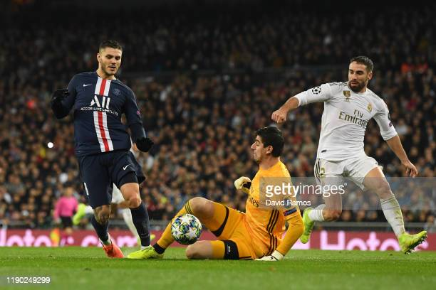 Mauro Icardi of Paris Saint-Germain is challenged by Thibaut Courtois of Real Madrid who receives a red card which is rescinded following a VAR...