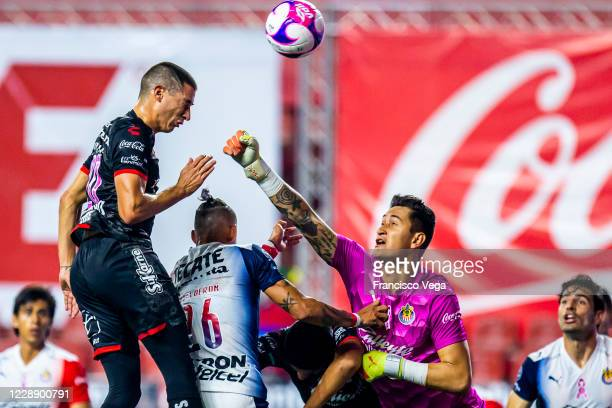 Mauro Lainez of Tijuana and Raul Guidiño of Chivas jump for the ball during the 13th round match between Tijuana and Chivas as part of the Torneo...