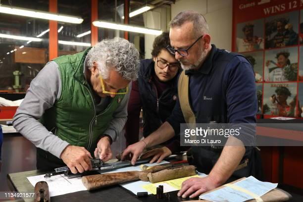 Mauro Perazzi looks at a shotgun with his son Nicola and a technician on April 4 2019 at the Perazzi Armi factory in Botticino Mattina a village in...