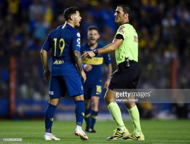 Mauro Zarate argues with teammate Edwin Cardona of Boca Juniors and referee Mauro Vigliano during a match between Boca Juniors and River Plate as...
