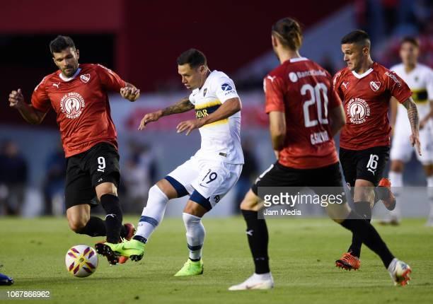 Mauro Zarate de Boca Juniors kicks the ball under pressure of Emanuel Gigliotti of Independiente during a match between Independiente and Boca...