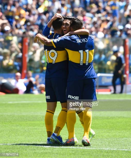 Mauro Zarate of Boca Juniors celebrates with teammates Emmanuel Reynoso and Eduardo Salvio after scoring the fourth goal of his team during a match...