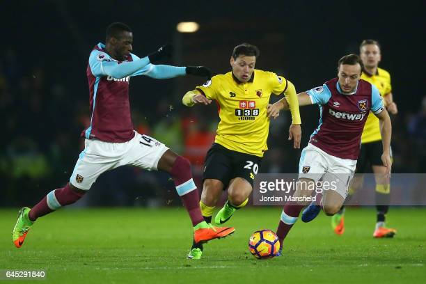 Mauro Zarate of Watford goes between Pedro Obiang and Mark Noble of West Ham United during the Premier League match between Watford and West Ham...