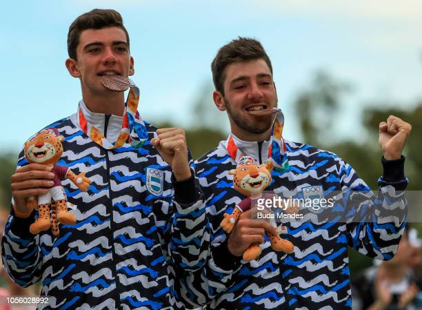 Mauro Zelayeta and Juan Bautista Amieva Tarditti of Argentina bite their Bronze medal in the podium of Mens Beach Volleyball during day 11 of Buenos...