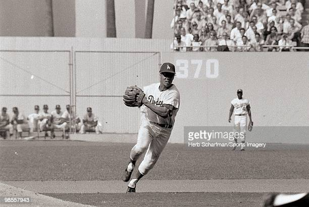 Maury Wills of the Los Angeles Dodgers fields a ball during the 1965 World Series against the Minnesota Twins at Dodger Stadium on October 10 1965 in...