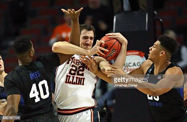 Maverick Morgan of the Illinois Fighting Illini gets tangled up while rebounding with Jamal Aytes and Yoeli Childs of the Brigham Young Cougars...