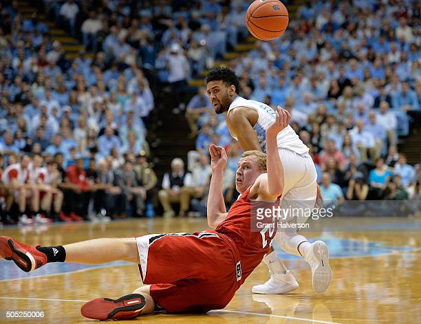 Maverick Rowan of the North Carolina State Wolfpack dives for a loose ball in front of Joel Berry II of the North Carolina Tar Heels during their...
