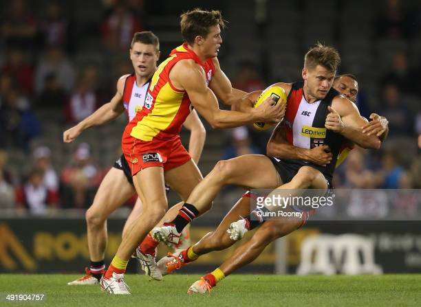 Maverick Weller of the Saints is tackled by David Swallow and Harley Bennell of the Suns during the round nine AFL match between the St Kilda Saints...
