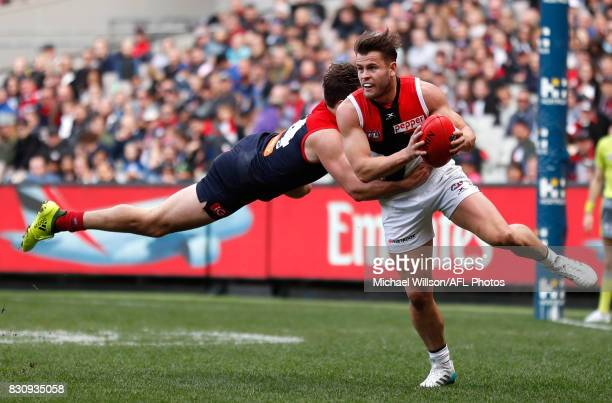 Maverick Weller of the Saints is tackled by Michael Hibberd of the Demons during the 2017 AFL round 21 match between the Melbourne Demons and the St...