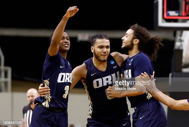 Max Abmas, Kevin Obanor and Kareem Thompson of the Oral Roberts Golden Eagles celebrate after defeating the Florida Gators in the second round game...