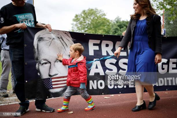 Max , accompanied by his mother Stella Moris, the lawyer and partner of WikiLeaks founder Julian Assange, walks past a banner with the face of his...