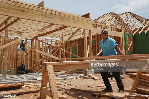 Max Alvarez works on building a new home to replace the one that was destroyed almost one year ago by a tornado on May 19 2014 in Moore Oklahoma On...