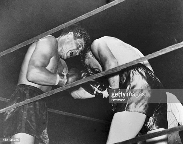 Max Baer stands in the corner with the ropes against his back holding off Jimmy Braddock during their heavyweight championship fight before 40000...