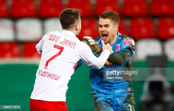 Max Besuschkow of Jahn Regensburg celebrates with team mate Alexander Meyer after scoring the winning penalty in the penalty shoot out during the DFB...