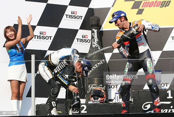 Max Biaggi of Italy sprays champagne at Makoto Tamada of Japan on the podium after the Japanese MotoGP at the Motegi Twin Ring curcuit on September...