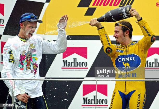 Max Biaggi of Italy sprays champagne over his compatriot Valentino Rossi after the latter won the Malaysian Motorcycle Grand Prix in Sepang 12...