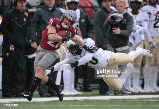Max Borghi of the Washington State Cougars carries the ball against Davion Taylor of the Colorado Buffaloes in the first half at Martin Stadium on...