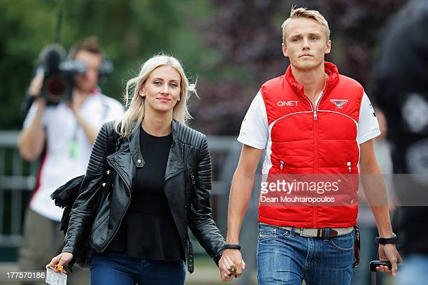 Max Chilton of Great Britain and Marussia and his girlfriend Chloe Roberts arrive in the paddock before the final practice session prior to...