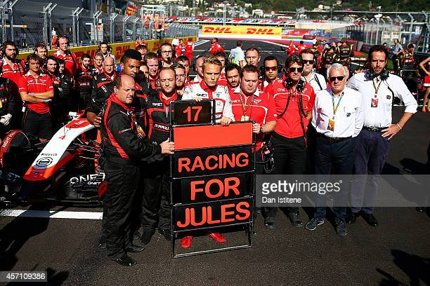 Max Chilton of Great Britain and Marussia stands with his team next to a tribute to Jules Bianchi of France and Marussia following his accident at...