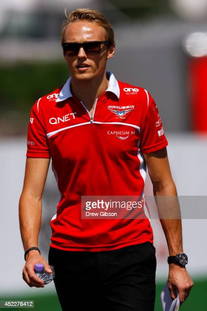 Max Chilton of Great Britain and Marussia walks along the track with members of his team during previews ahead of the German Grand Prix at...