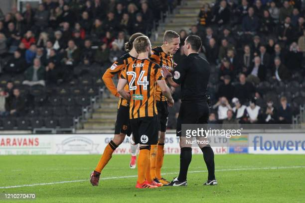 Max Clark and Jackson Irvine look on as Hull City's Michael Dawson remonstrates with Referee Tim Robinson after he dismissed Michael Hector during...
