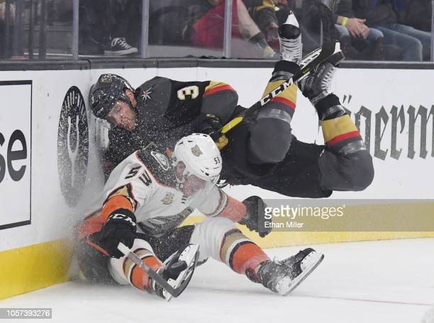 Max Comtois of the Anaheim Ducks and Brayden McNabb of the Vegas Golden Knights crash into the boards as they go after a loose puck in the first...