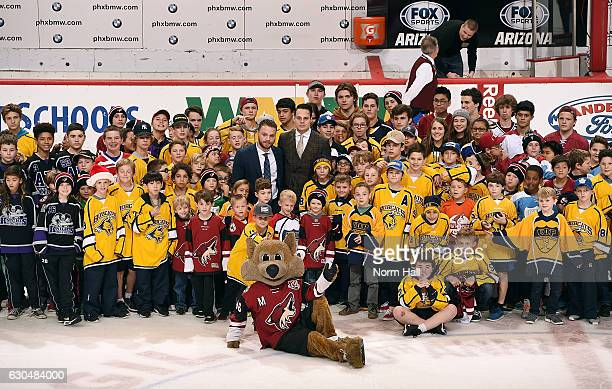 Max Domi of the Arizona Coyotes and Auston Matthews of the Toronto Maple Leafs pose with a group of Arizona youth hockey players following a game...