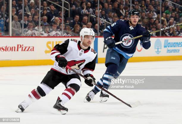 Max Domi of the Arizona Coyotes and Marko Dano of the Winnipeg Jets keep an eye on the play during first period action at the Bell MTS Place on...