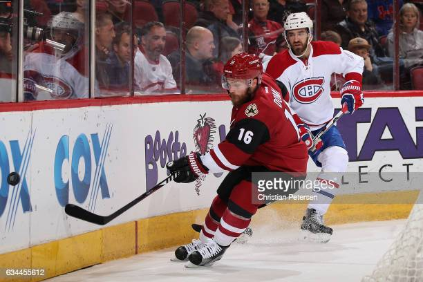 Max Domi of the Arizona Coyotes attempts to play the puck ahead of Greg Pateryn of the Montreal Canadiens during the first period of the NHL game at...